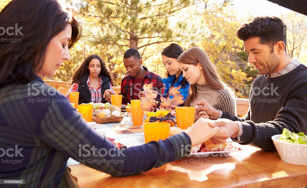 Friends at a table at a barbecue saying grace before eating stock photo