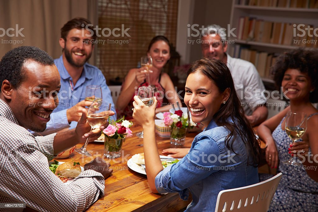 Friends at an evening dinner party, looking at camera stock photo