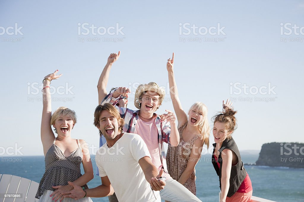 Friends at beach with arms raised royalty-free stock photo