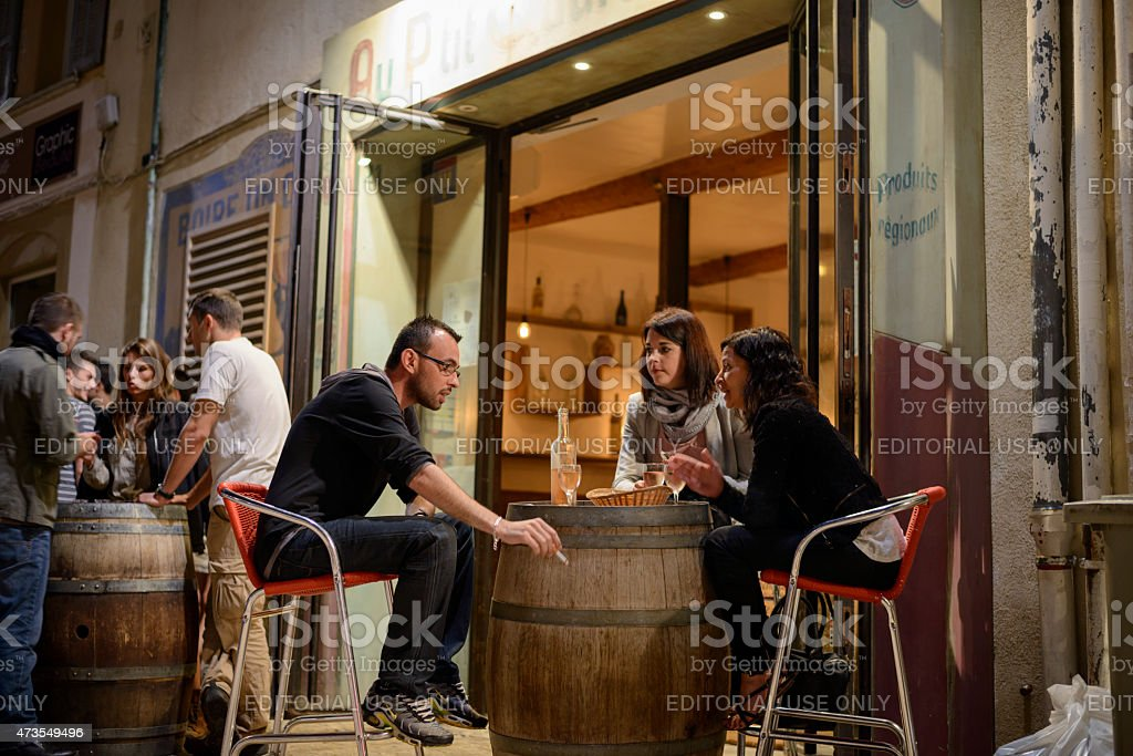 Friends at cafe at night in Aix-en-Provence, France stock photo