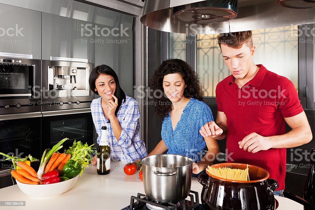 Friends at Cooking Party Italian Spaghetti Dinner in Modern Kitchen stock photo