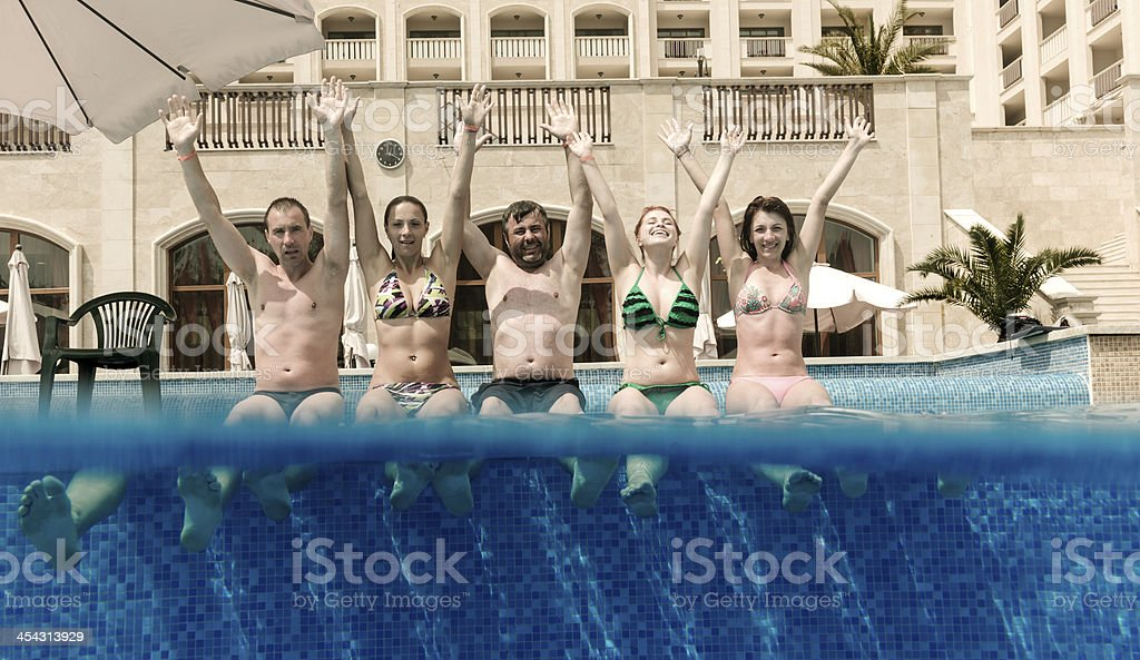 friends at edge of swimming pool royalty-free stock photo