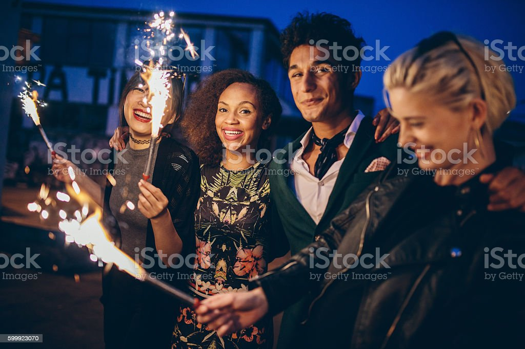 Friends at night with fireworks enjoying party stock photo