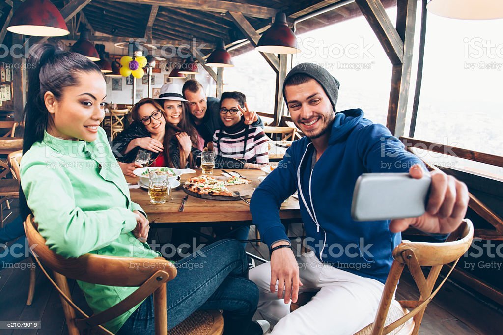 Friends at restaurant making selfie stock photo