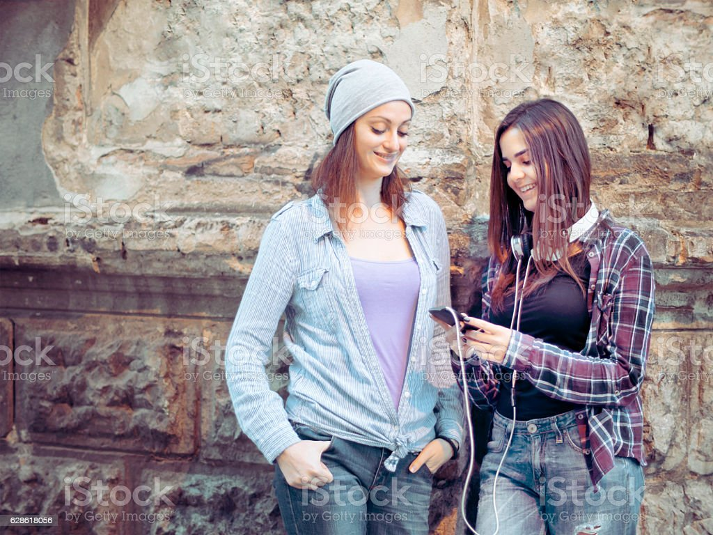 Friends at street listening music together stock photo