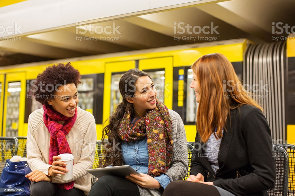 Friends at subway station waiting for train stock photo