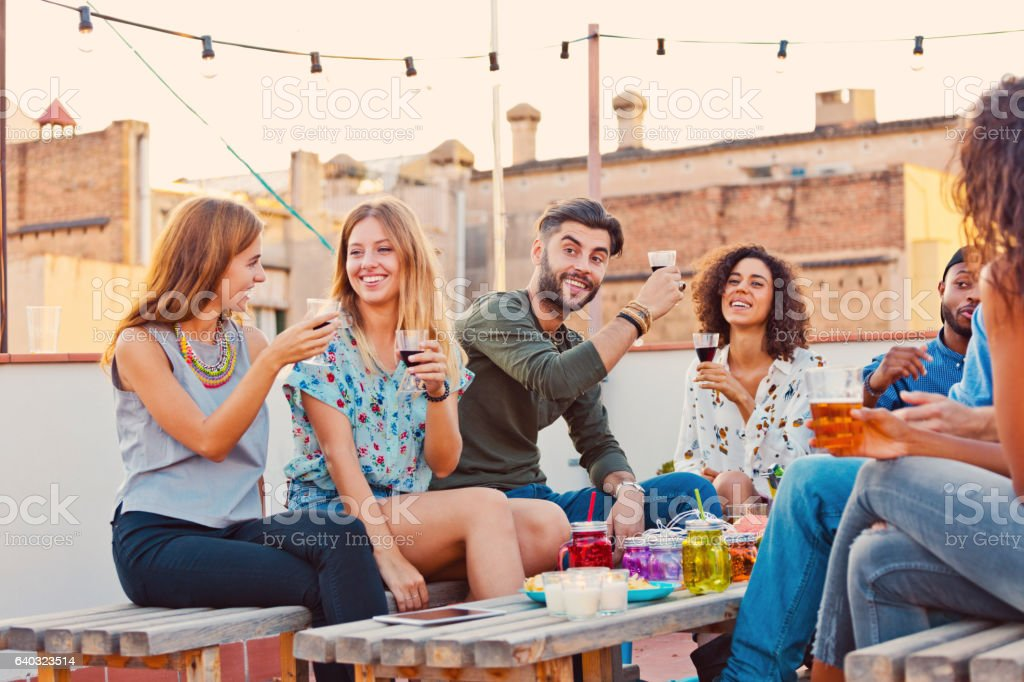 Friends at the rooftop party drinking red wine stock photo