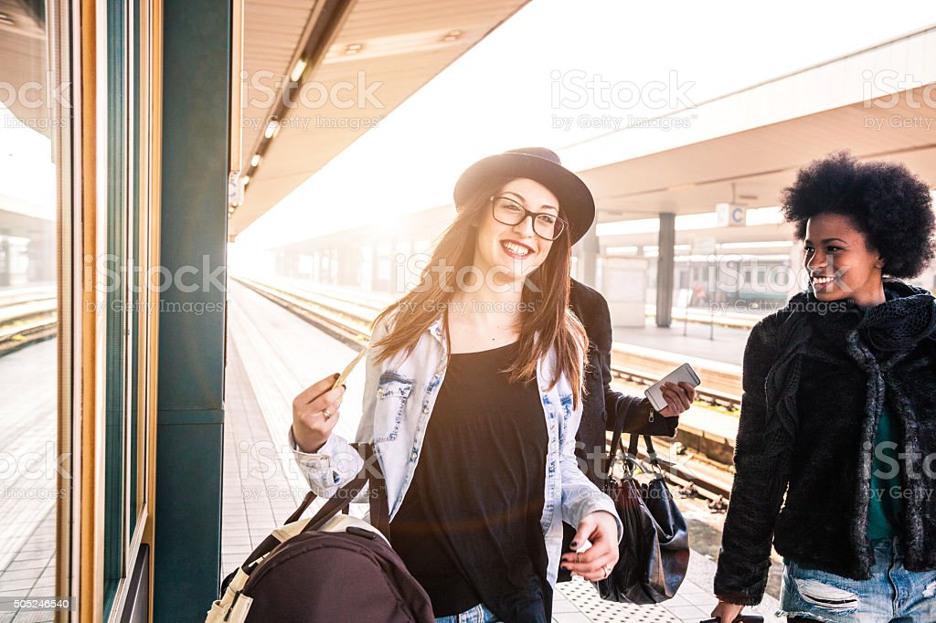 Friends at train station platform, tourist and commuters arriving stock photo