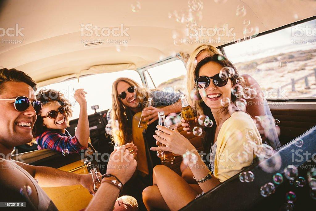 Friends blowing bubbles on roadtrip stock photo