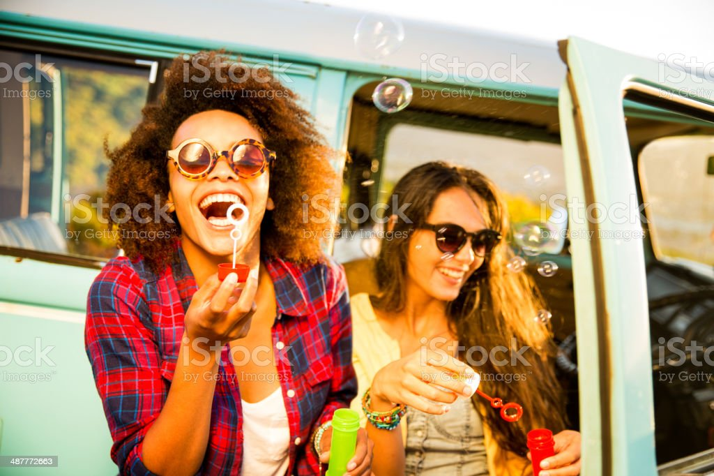 Friends blowing bubbles on roadtrip royalty-free stock photo