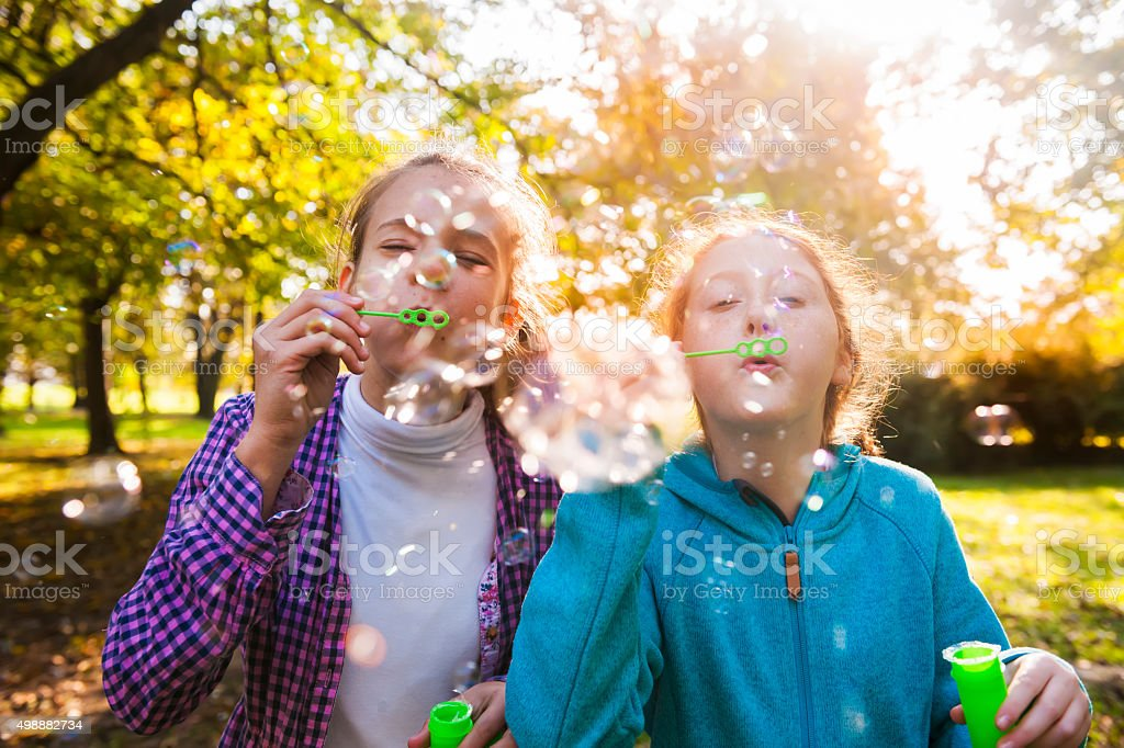 Friends blowing bubbles outdoors stock photo
