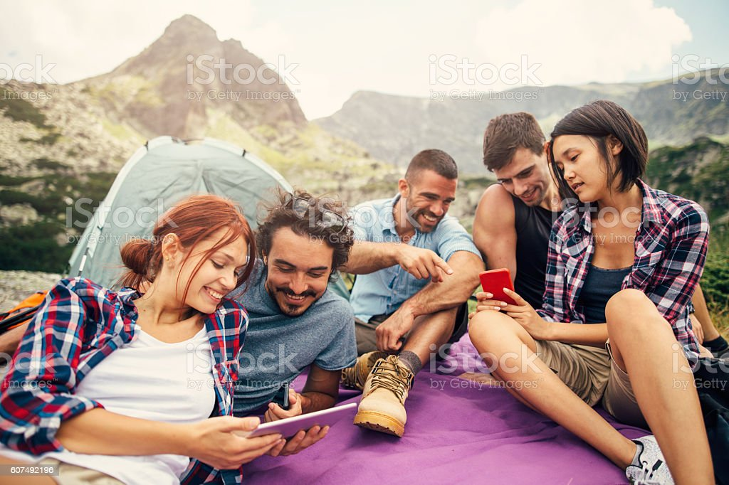Friends browsing the net in the mountain stock photo