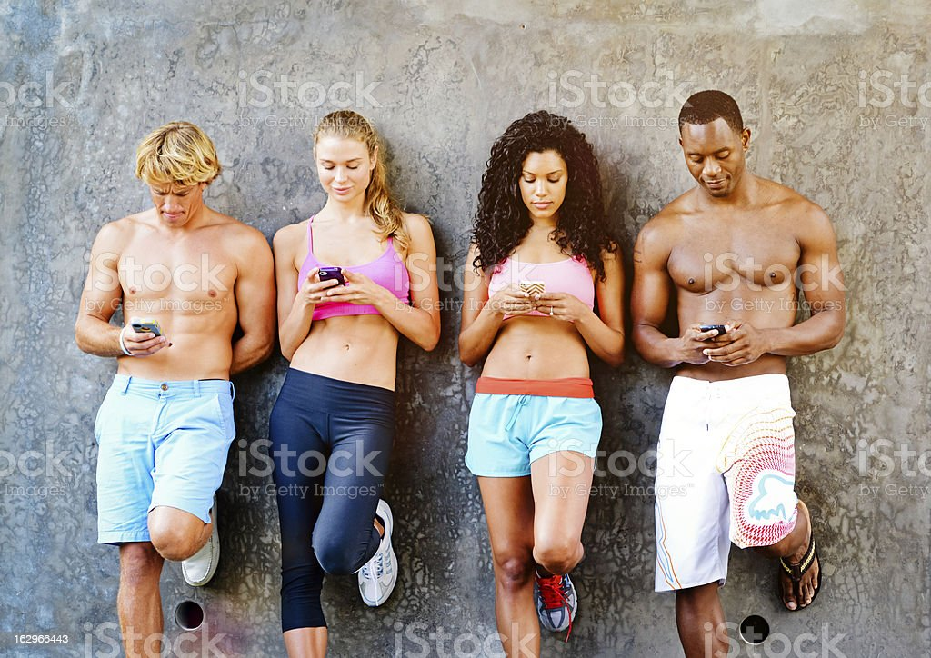 Friends busy checking their smartphones royalty-free stock photo