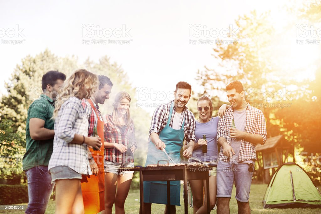 Friends camping and having a barbecue stock photo