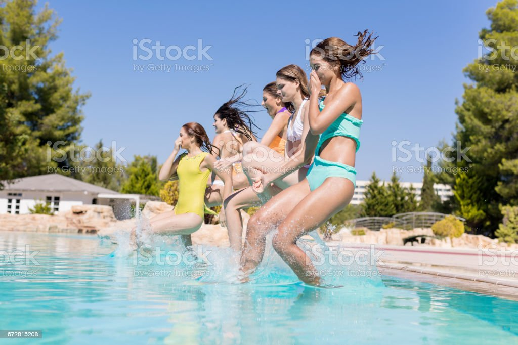 Friends cannon jumping into pool stock photo