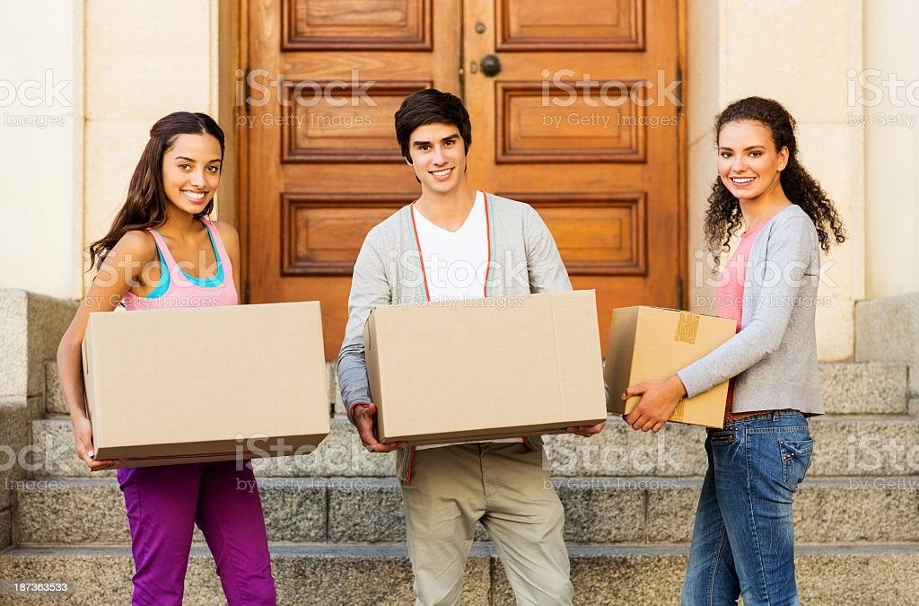 Friends Carrying Cardboard Boxes In Front On House stock photo