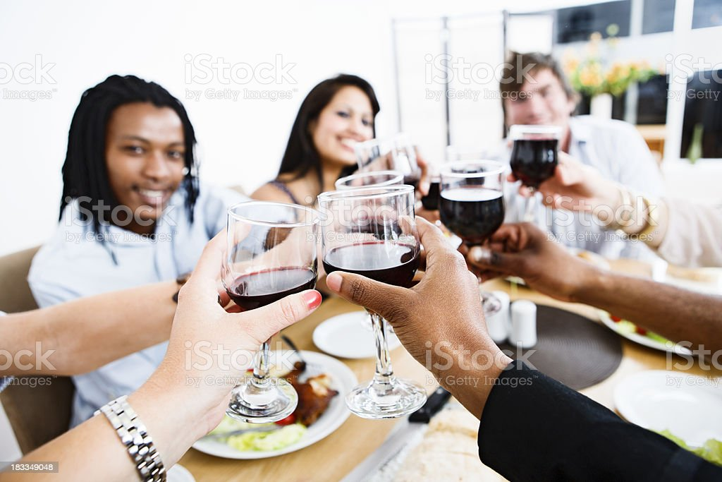 Friends celebrating at meal with a toast in red wine royalty-free stock photo