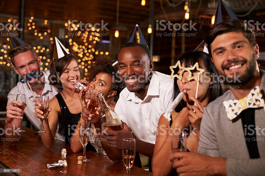 Friends celebrating New Year's Eve at a party in a bar stock photo