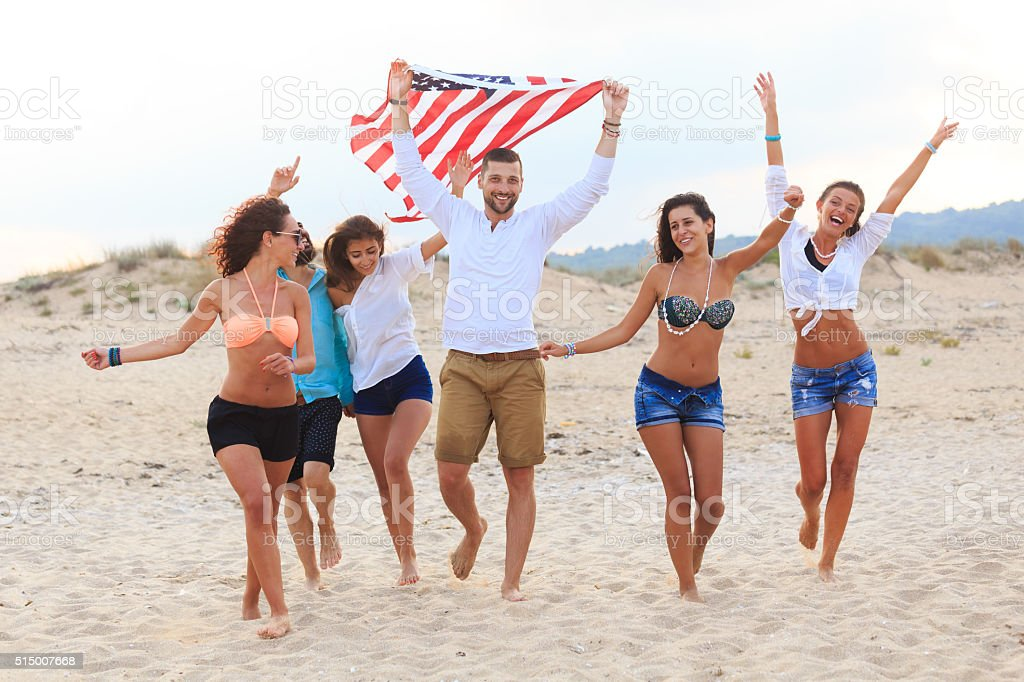 Friends celebrating on beach with flag stock photo