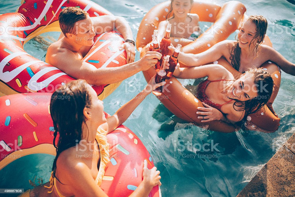 Friends celebrating summer in a pool with bottled beverages stock photo