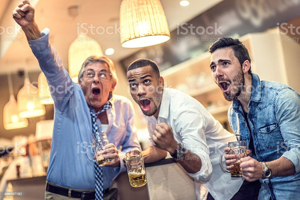 Friends celebrating their team scoring in a bar stock photo