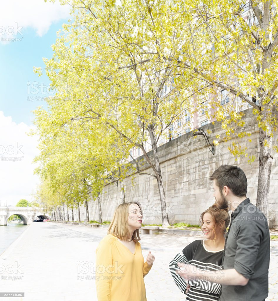 Friends chatting by the River Seine, Paris stock photo