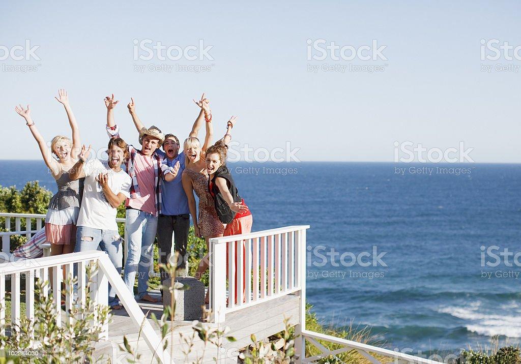 Friends cheering on patio near ocean royalty-free stock photo