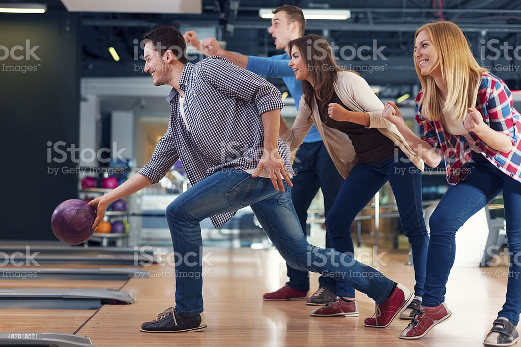 Friends cheering their friend while throwing bowling ball stock photo