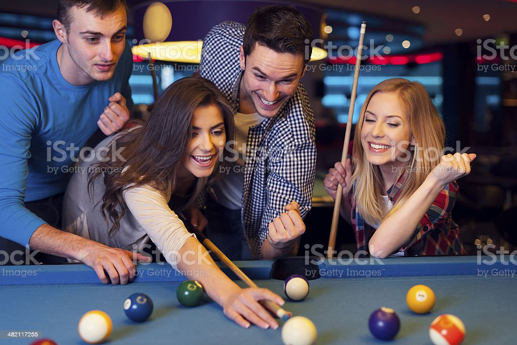 Friends cheering while their friend aiming for billiards ball stock photo