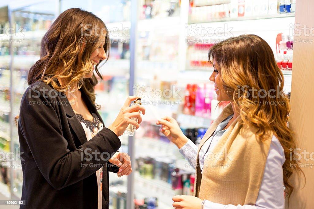 Friends choosing perfume stock photo