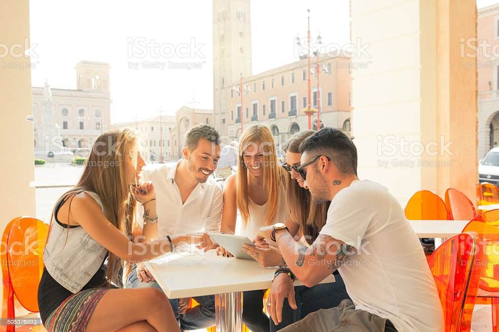 Friends choosing where to go for holidays stock photo