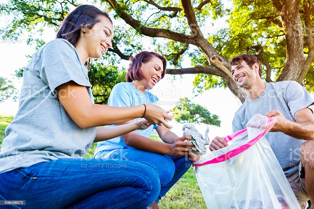 Friends collect trash during community cleanup stock photo