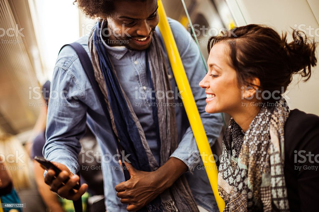Friends commuting together in subway train stock photo