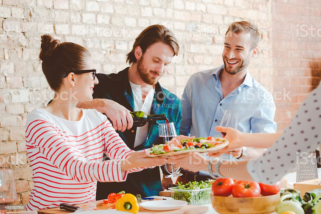 Friends cooking pizza together in the modern kitchen stock photo