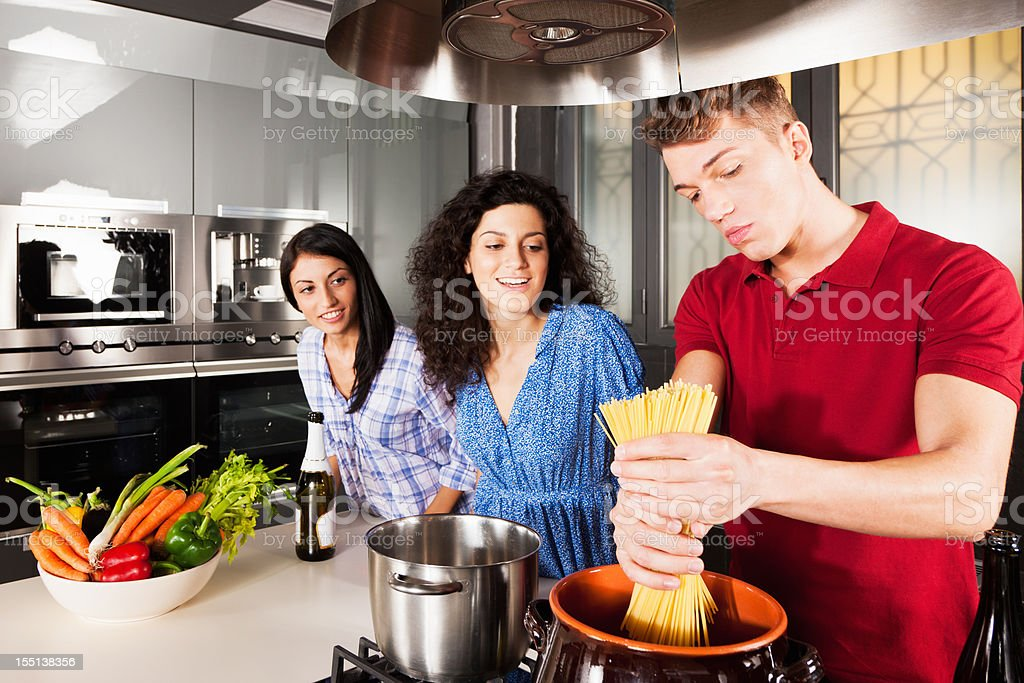 Friends Cooking Together in Modern Kitchen stock photo