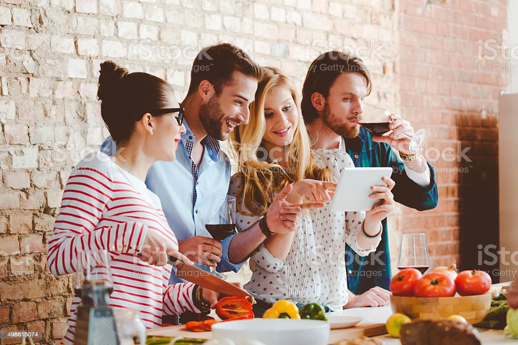 Friends cooking together in the modern kitchen, using digital tablet stock photo
