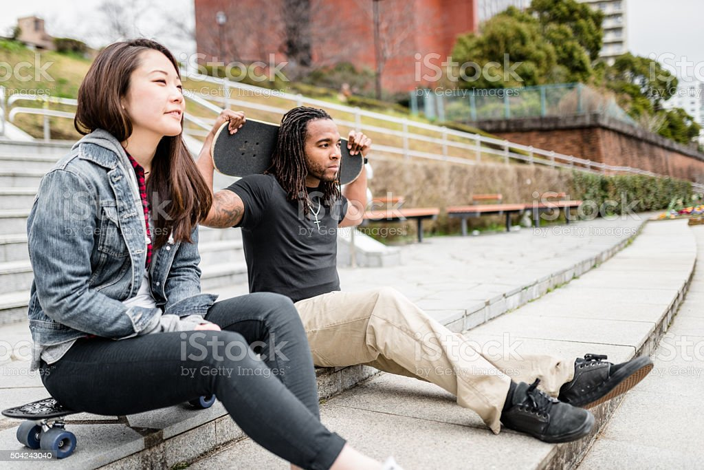 friends couple relaxing after had skating stock photo