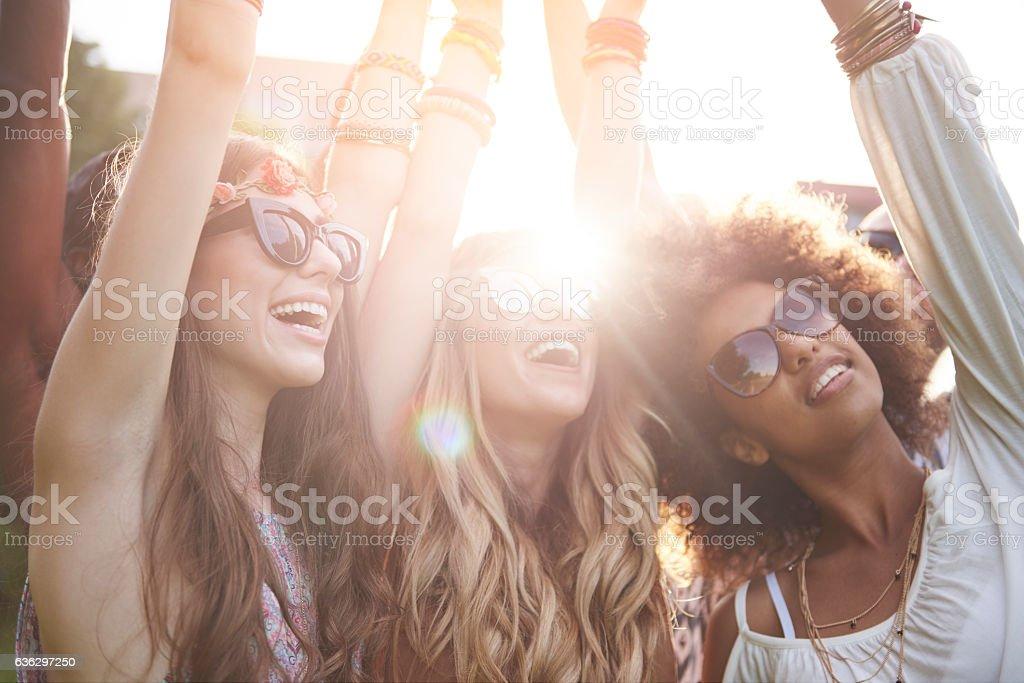 Friends dancing among bright sunbeams stock photo