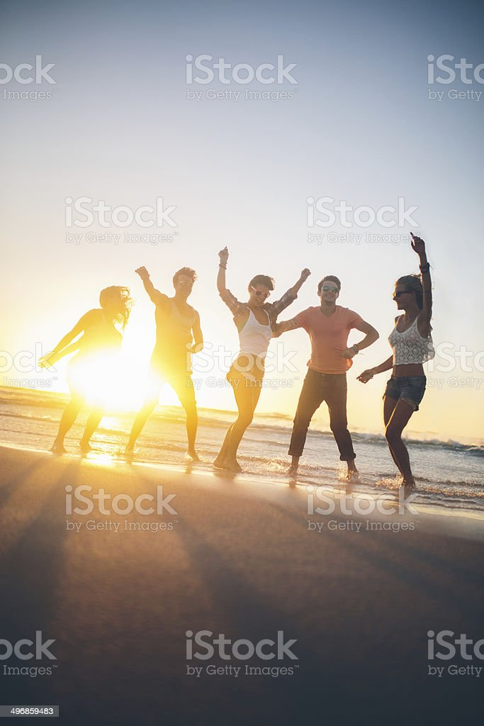Friends dancing on beach in sunset royalty-free stock photo