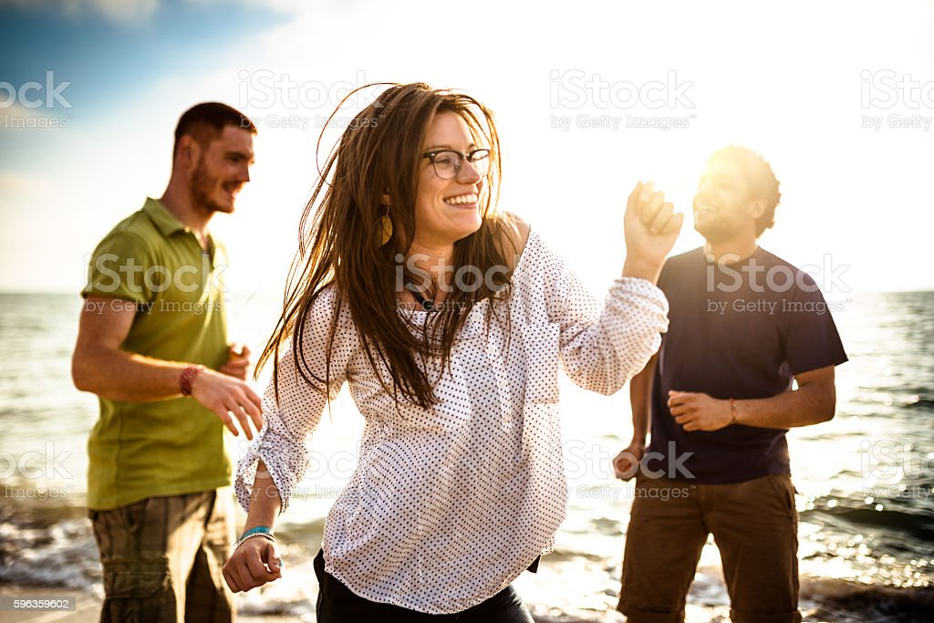 friends dancing on the beach at dusk for a party stock photo