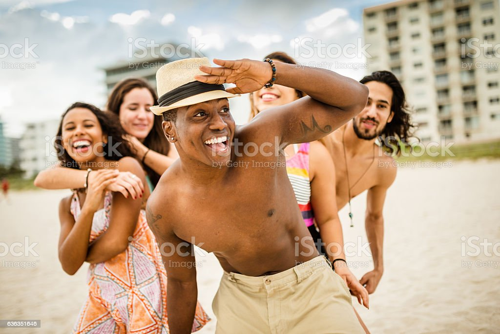 friends dancing on the beach for a party stock photo