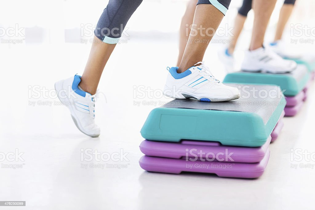Friends Doing Aerobics Using Stair Stepper In Gym royalty-free stock photo
