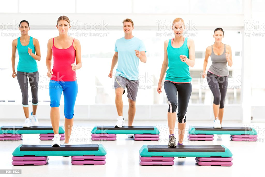 Friends Doing Aerobics Using Stair Steppers In Gym stock photo