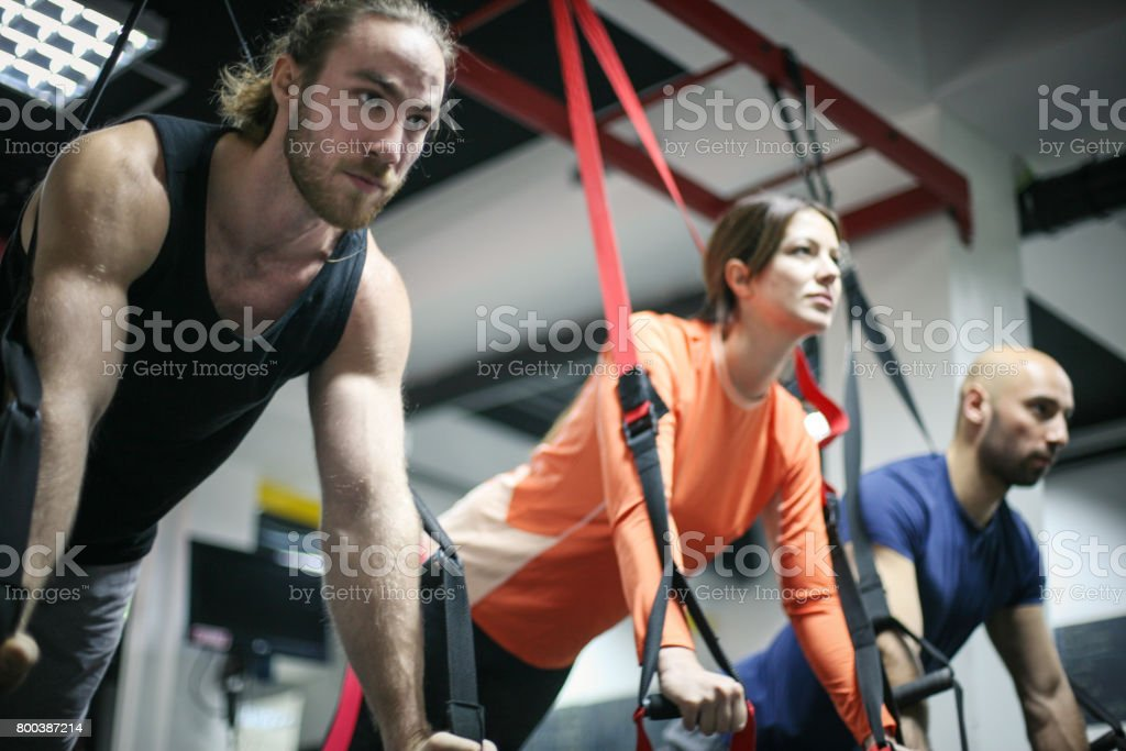 Friends doing exercises in a gym with straps. Three friends in the gym. stock photo