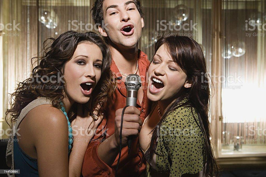 Friends doing karaoke stock photo