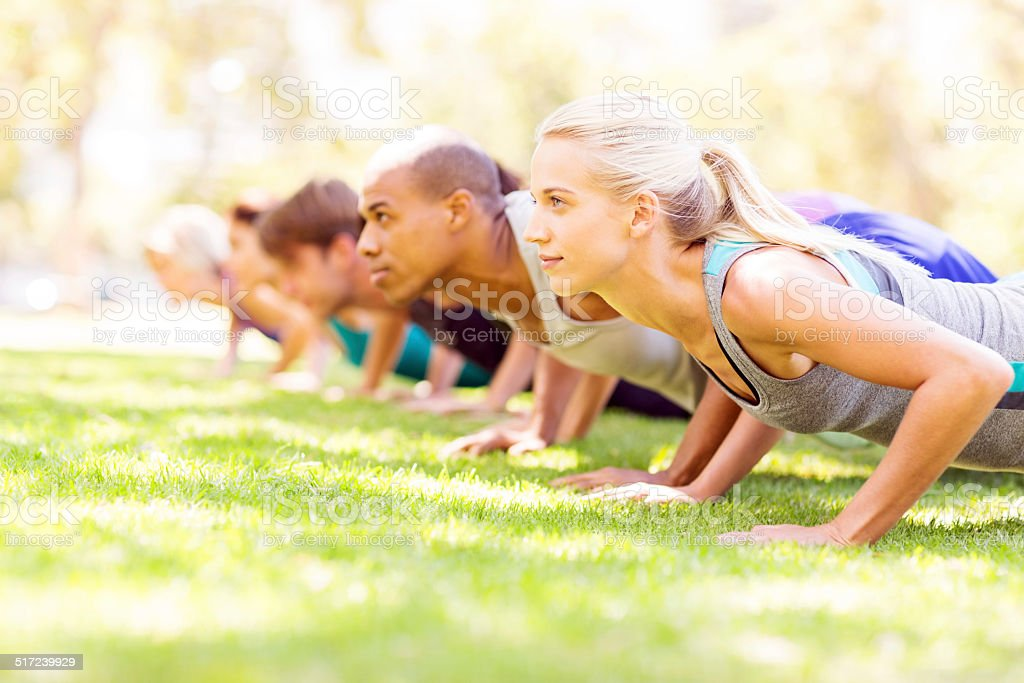 Friends Doing Push-Ups In Park stock photo