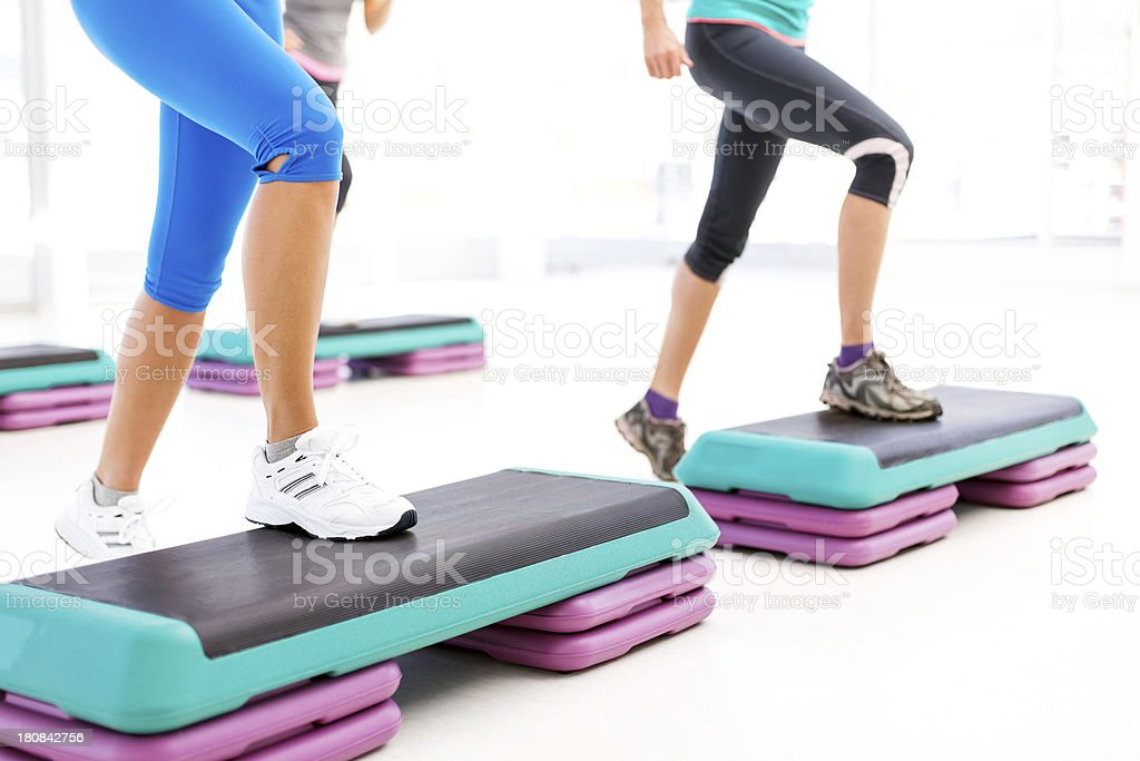 Friends Doing Step Aerobics In Health Club stock photo