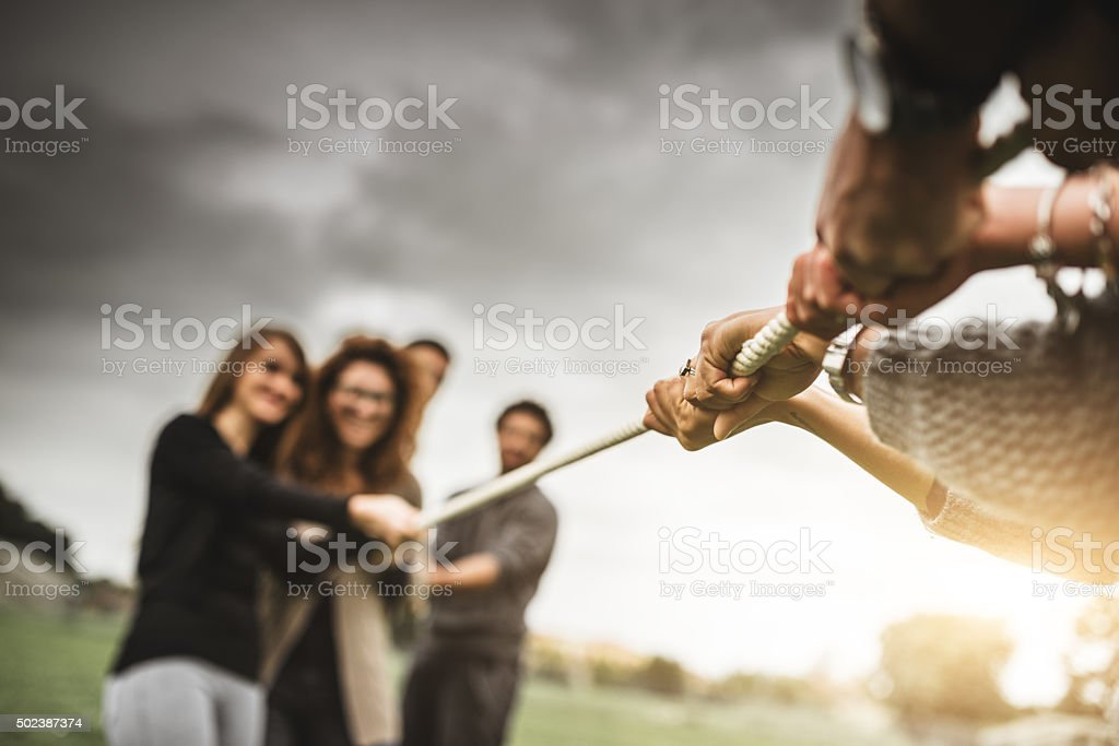 Friends doing the Tug of war - teamwork stock photo