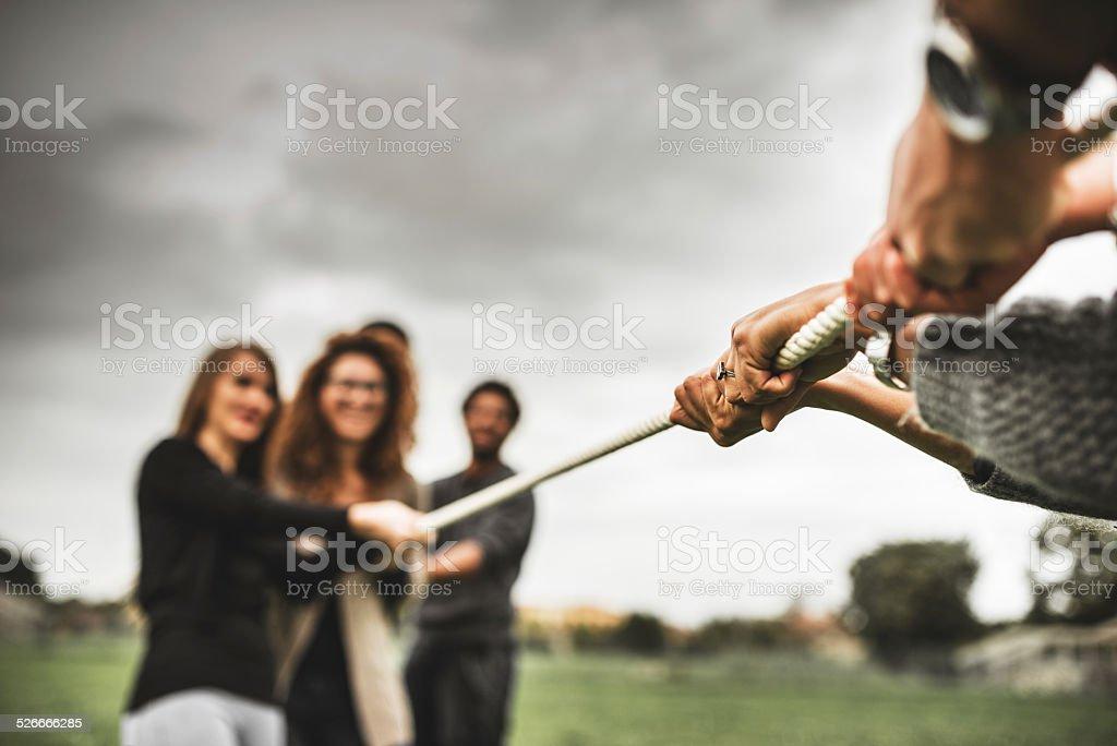 Friends doing the Tug of war - teamwork stock photo