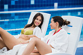 Friends dressed in bathrobes and bikini relaxing at spa next